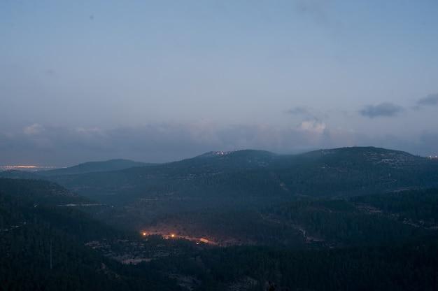 Landschap van heuvels bedekt met bossen en lichten onder een bewolkte hemel tijdens de avond