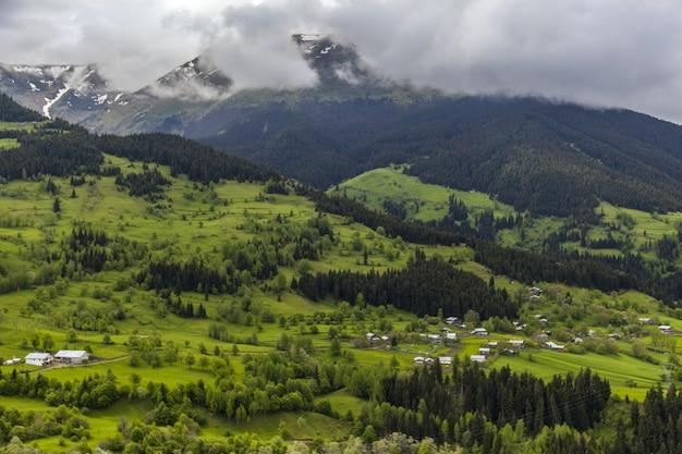 Landschap van heuvels bedekt met bossen, sneeuw en mist onder een bewolkte hemel overdag