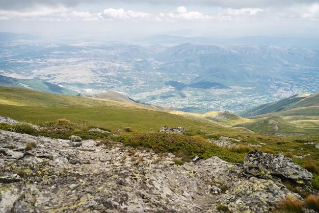 Landschap van heuvels bedekt met groen met rotsachtige bergen onder een bewolkte hemel op de achtergrond