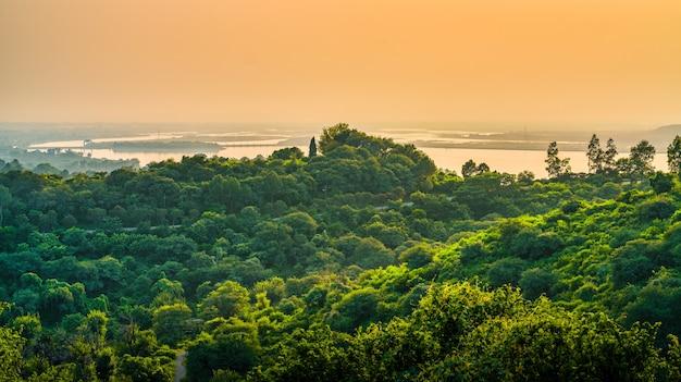 Landschap van heuvels bedekt met groen, omringd door de zee onder een bewolkte hemel tijdens de zonsondergang