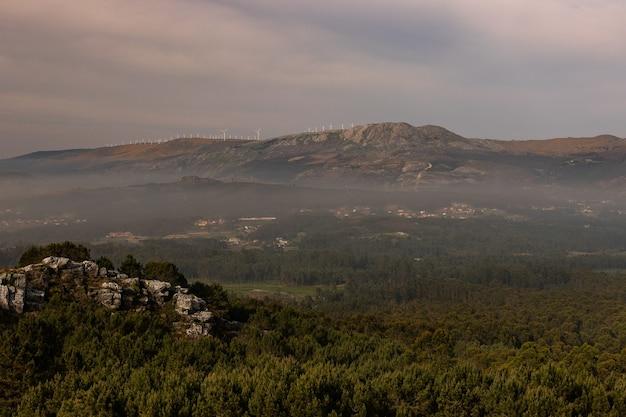 Landschap van heuvels en rotsen bedekt met groen en mist onder een bewolkte hemel in de avond