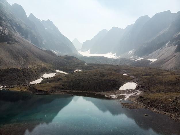 Landschap van hoge berg met meer en hoge piek.