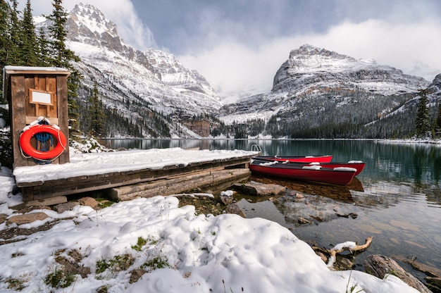 Landschap van lake o'hara met rode kano in houten dock op winter in yoho national park