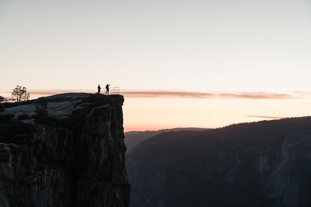 Landschap van mensen die bovenop een rotsformatie staan en de schoonheid van de natuur bewonderen