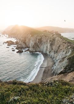 Landschap van oceaangolven die tijdens zonsopgang naar de rotsformatie gaan
