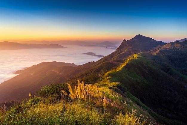Landschap van ochtendmist en bergen bij zonsopgang.