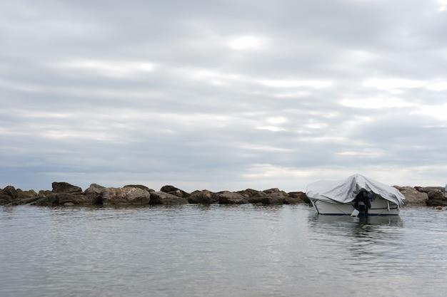 Landschap van overdekte boot op de zee onder een bewolkte hemel