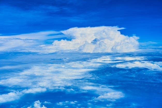 Landschap van pluizige witte wolken op een donkerblauwe hemel. uitzicht vanuit het vliegtuig op grote hoogte.