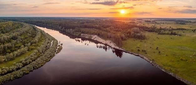 Landschap van rivier in de avond in het licht van de ondergaande zon