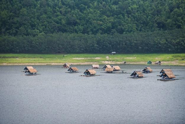 Landschap van rivierberg en bamboe woonbootvlot drijvend op rivieroever