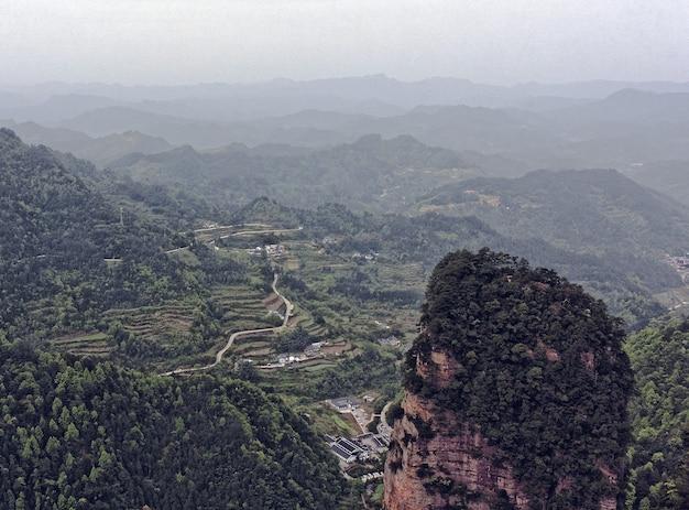 Landschap van rotsachtige bergen bedekt met groen en mist - ideaal voor behang