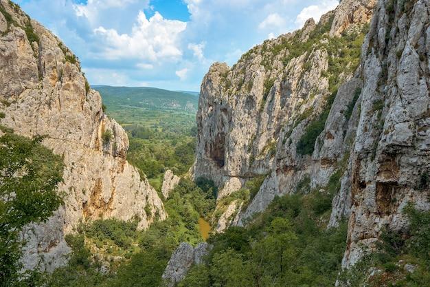 Landschap van rotsen bedekt met groen onder een blauwe lucht en zonlicht