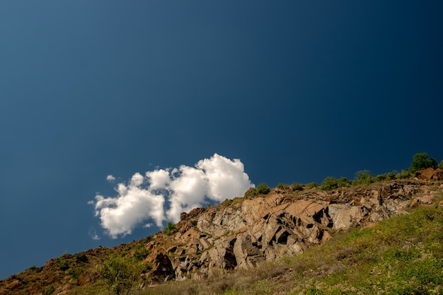 Landschap van rotsen bedekt met groen onder het zonlicht en een blauwe lucht