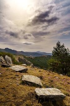 Landschap van rotsen met groene planten, dramatische hemel met wolken en verre bergen.