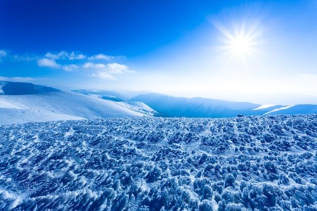 Landschap van sneeuwwintervallei en bergen en zon hierboven op heldere ijzige winterdag