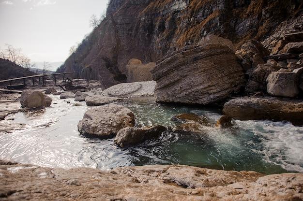 Landschap van snelle bergrivier die onder rotsen en stenen in martvili-canion stromen