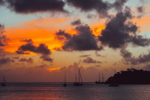 Landschap van zonsondergang met een silhouet van bergen en boten in de zee