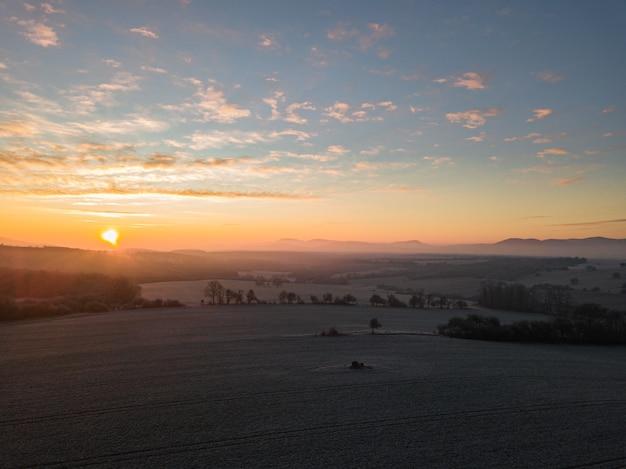 Landschap van zonsondergang met uitzicht op de bomen op het veld en de bergen