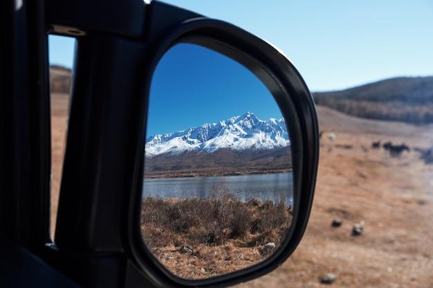 Landschap weerspiegeld in de achteruitkijkspiegel van een auto in altai