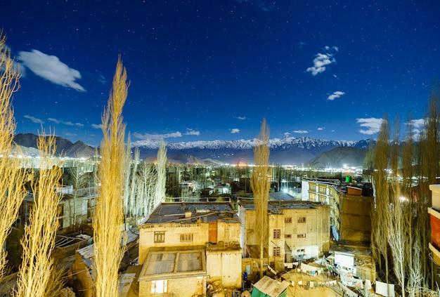 Landschapsbeeld van leh-stad met bergenmening en sterren in de hemel bij nacht