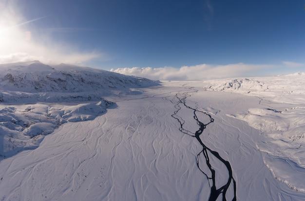 Landschapsfoto van besneeuwde bergen onder bewolkte hemel overdag