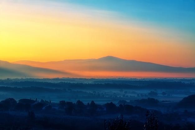 Landschapsfotografie van bomen dichtbij berg tijdens oranje zonsondergang