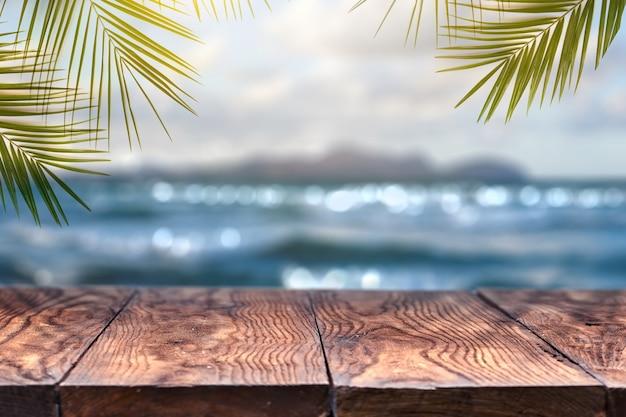 Landschapsmening met oud houten tafelblad en kokosblad over vage blauwe zee en wit zandstrand met heldere blauwe hemelachtergrond. concept zomer ontspannen en feesten.