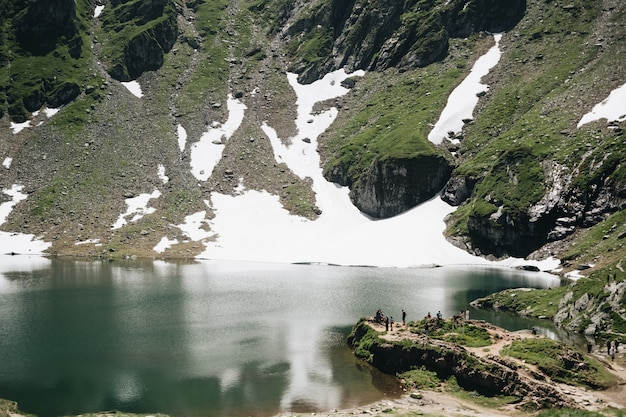 Landschapsmening van balea-meer in de bergen van roemenië en fagaras-in de zomer met sneeuwpieken
