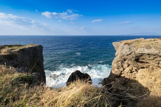 Landschapsmening van de klip met de blauwe hemel, de wolk en de blauwe zee