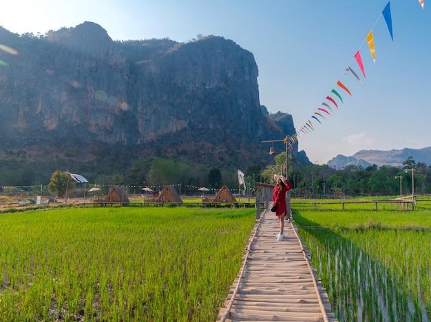Landschapsvrouw die zich op houten brug over groen rijstveld bevinden die grote bergmening (phu pha man) in khonkaen, thailand bekijken