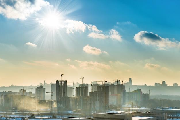 Landschapszonsondergang in de stad met blauwe lucht, zon en industriële kranen