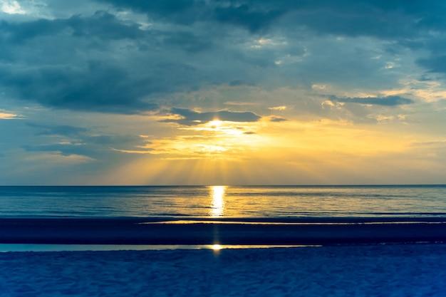 Landschapszonsondergang op het strand met lichte gloed op de oceaan in dwarsproceskleur.