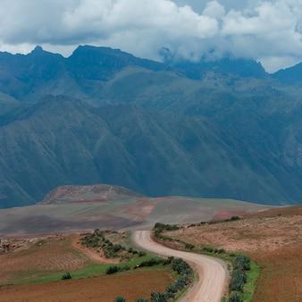 Landweg die door een landschap met een bergketen op de achtergrond, heilige vallei, cusco-gebied, peru overgaan
