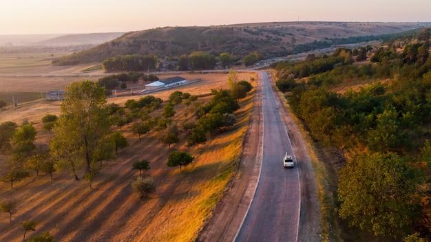 Landweg en rijdende auto bij zonsopgang, velden, heuvels bedekt met bomen