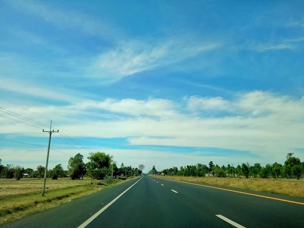 Landweg met geel padieveld, elektrische post, groene boom en blauwe hemel met witte wolk.