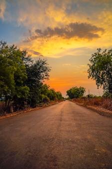 Landweg met zonsondergang op de achtergrond. grijze weg met bomen aan beide zijden en heldere kleurrijke avondlucht zonder voertuigen.