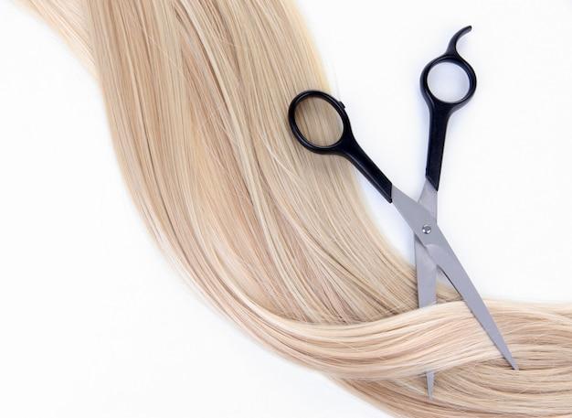 Lang blond haar en schaar geïsoleerd op wit