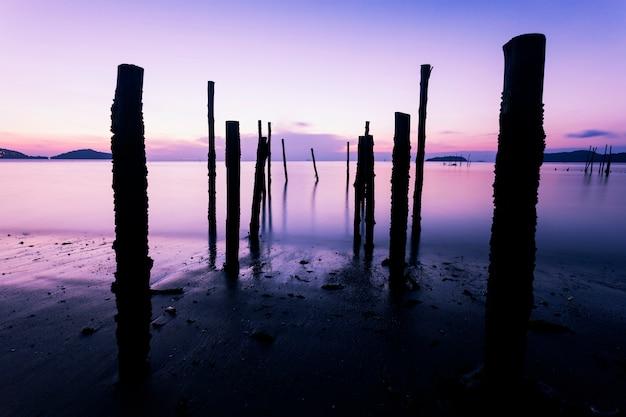 Lang blootstellingsbeeld van dramatisch hemelzeegezicht met oude houten pool in de overzeese zonsondergang