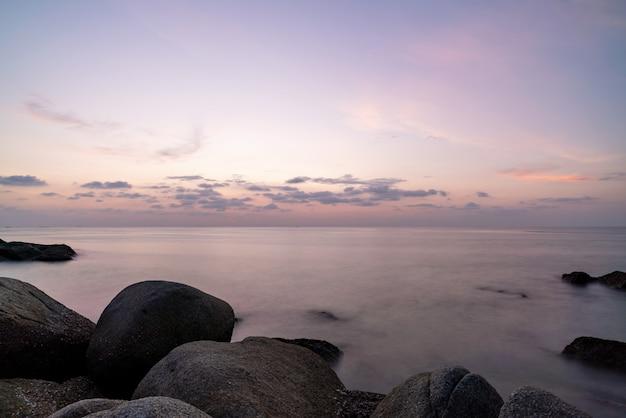 Lang blootstellingsbeeld van dramatisch hemelzeegezicht met rots in de het landschapsaard van de voorgrondzonsondergang.