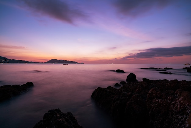 Lang blootstellingsbeeld van dramatisch hemelzeegezicht met rots in zonsonderganglandschap