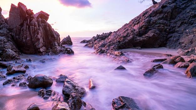 Lang blootstellingsbeeld van dramatische hemel en golfzeegezicht met rots op de achtergrond van het zonsonderganglandschap