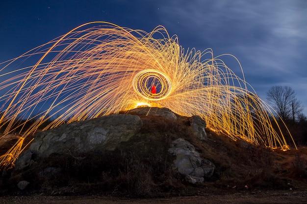 Lang blootstellingsschot van de mens die zich op rotsachtige heuvel spinnende staalwol in cirkel bevinden die vuurwerkdouches maken