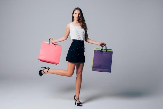 Lang gelukkig meisje in schoenen met hoge hakken houdt been omhoog en verschillende boodschappentassen op wit wordt geïsoleerd