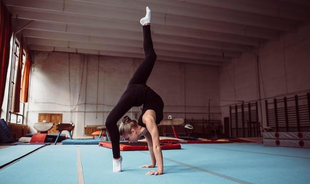 Lang geschoten blonde vrouw die voor gymnastiekkampioenschap traint