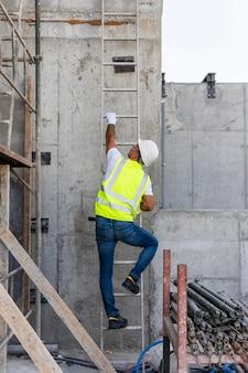 Lang geschoten man die de trap op een bouwplaats beklimt