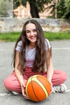 Lang geschoten meisje dat een basketbal buiten houdt