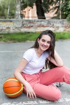 Lang geschoten meisje dat een basketbal houdt