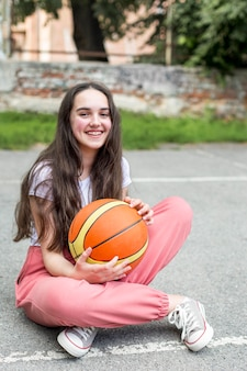 Lang geschoten meisje dat een basketbal in openlucht houdt