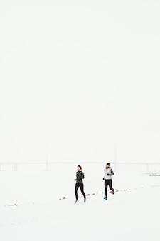 Lang geschoten mensen die in de sneeuw rennen