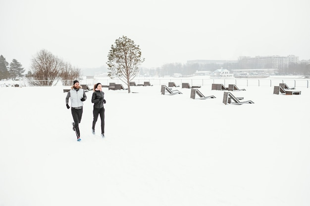 Lang geschoten mensen die in de winter in de natuur rennen